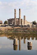 Temple of Leto, built 3rd century BC, its columns reflected in a pool of flood water, Letoon, near Xanthos, Antalya, Turkey. This is the largest and best-preserved of the 3 temples on the site. It was built of very fine limestone, creating the illusion of marble. An ionic peripteros of 11x6 columns surrounded the cult room or cella, which was decorated with a Corinthian colonnade. The Letoon or Sanctuary of Leto was the sacred cult centre of Lycia, its most important sanctuary, and was dedicated to the 3 national deities of Lycia, Leto and her twin children Apollo and Artemis. Leto was also worshipped as a family deity and as the guardian of the tomb. The site is 10km South of the ancient city of Xanthos in Lycia, near the modern-day village of Kumluova, Fethiye. Founded in the 6th century BC, the Greek site also flourished throughout Roman times, and a church was built here in the Christian era. The site was abandoned in the 7th century AD. Picture by Manuel Cohen