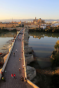 Roman bridge spanning river Rio Guadalquivir with Mezquita cathedral buildings, Cordoba, Spain