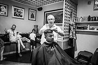 TAORMINA (ME) - 8 SETTEMBRE 2018: Carmelo, un barbiere di Taormina, taglia i capelli a un immigrato che abita e lavora a Taormina da anni, a Taormina, l'epicentro dell'avanzata della Lega in Sicilia con il 23,52%, l'8 settembre 2018. Sullo sfondo Rudi, un cliente toarminese che ha votato la Lega alle ultime elezioni politiche, spiega il perché sostiene Matteo Salvini.