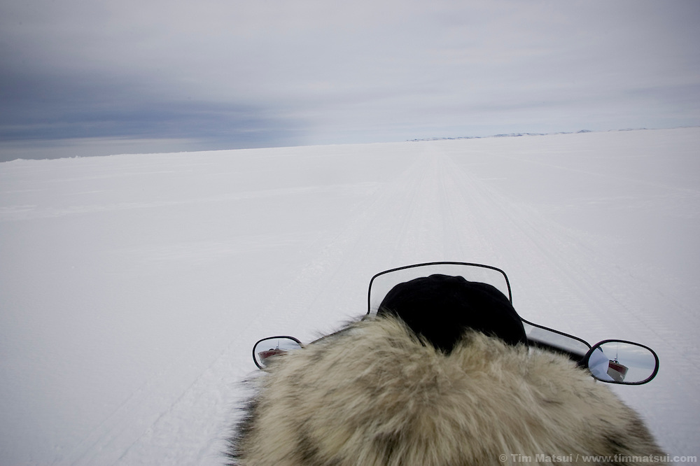 May 3, 2008 -- Kivalina, AK, U.S.A..From the back seat of Austin Swan's snow mobile as he tows a boat to his whaling camp 12 miles from the 400 person native village of Kivalina, Alaska, and two miles out onto melting pack ice. Kivalina is suing 20 oil companies for property damage related to global warming; the ocean pack ice forms later and melts earlier, leaving the town vulnerable to erosive winter storms and endangering their traditional subsistence lifestyle. (Photo by Tim Matsui)