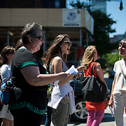 """June 21, 2014 - New York, NY : <br /> The city was flooded with music on Saturday as Make Music New York brought more than 1,300 free concerts to the city's streets and parks. The annual festival's program included """"And Death Shall Have No Dominion,"""" a piece by composer Pete M. Wyer, honoring the centenary of the birth of the poet Dylan Thomas. The piece -- a participatory singing event -- was performed by a synchronized headphone choir. The choir's singers began in smaller groups around lower Manhattan and culminated in a meeting in Battery Park City. The sopranos, who began their walk at Bleecker Playground in Greenwich Village, pause before crossing the West Side Highway on their way to the meeting point in Nelson A. Rockefeller Park. Singing, from foreground left, are Susan Lerner, Brigid Kegel, and Pamela Cook. CREDIT: Karsten Moran for The New York Times"""