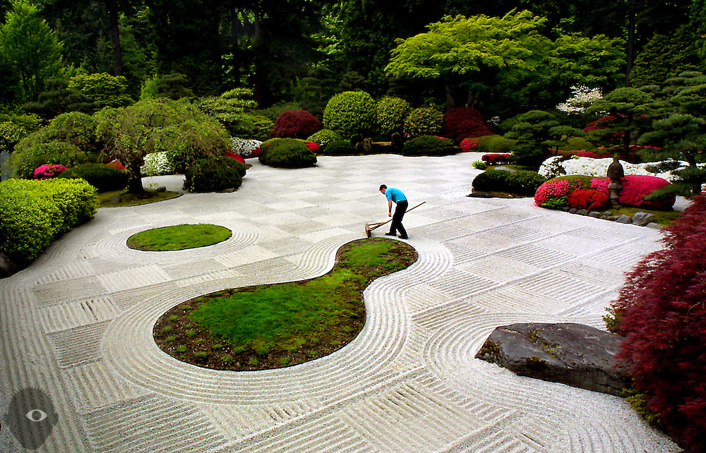 David Deese rakes a flat garden of sand and stone at the Japanese Garden in Portland, Oregon. This garden features two islands which depict a sake cup and gourd-shaped bottle, signifying pleasure and a wish for the visitor's happiness.