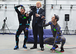 """© Licensed to London News Pictures. 04/04/2013. London, UK (Left to right) Actors Matt Cross, Boris Johnson. Boris Johnson the Mayor of London, visits Ealing studios today, 4th April 2013, where he announced his plans to boost London's TV, Animation and Film industries, capitalising on the new tax relief brought in by the Chancellor (from 1st April 2013) to bring major jobs and investment to the capital. He toured the Studios and spent time in the """"Imaginarium"""", where he had a go at mastering 'performance capture'. . Photo credit : Stephen Simpson/LNP"""