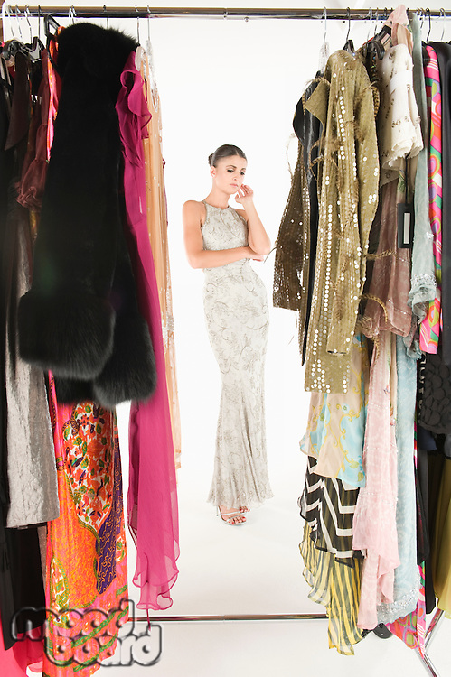 View through clothing rail of woman in long evening dress