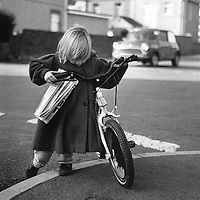 A girl pushes her bicycle on her way home.  South Wales