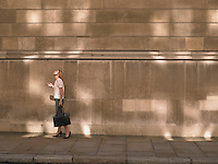 Woman standing by wall looking up