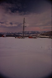Stock photo of a snow covered work over drilling rig on site in the mountains of Colorado