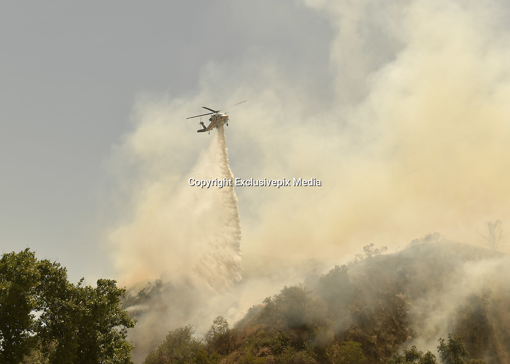 June 20, 2016 - Duarte, California, U.S. -A helicopter drops water on the Fish Fire Monday. ..The Fish Fire burns above Duarte and Los Angeles County. The Reservoir Fire also started nearby during record heat in the Southwest. The fire was 1,400 acres at 2:50pm.<br /> &copy;Exclusivepix Media
