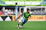 Cristian Roldan #7 of Seattle Sounders moves the ball against Luis Caicedo #27 of New England Revolution during a MLS soccer match on Saturday, Aug. 10, 2019, in Seattle. The teams played tp a 3-3 tie. (Alika Jenner/Image of Sport)
