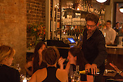 New York, NY, Sept. 10....shots of the restaurant Estela. Sommelier Thomas Carter pouring a bottle of wine for a table of diners.