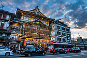 Traffic in street by Kyoto's Minamiza Kabuki Theatre, a prime place in Japan to see kabuki. It is located in a grand building on the corner of Shijo-dori and Kawabata-dori in Gion district, Kyoto, Japan.