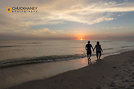 Couple holding hands at sunset along Gulf of Mexico in Sanibel Island, Florida, USA MR