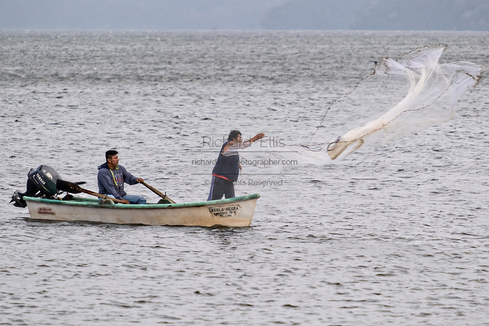 Fishermen use a cast net at Lake Catemaco in Catemaco, Veracruz, Mexico. The tropical freshwater lake at the center of the Sierra de Los Tuxtlas, is a popular tourist destination and known for free ranging monkeys, the rainforest backdrop and Mexican witches known as Brujos.