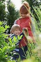 Mother embracing son (5-6) in garden