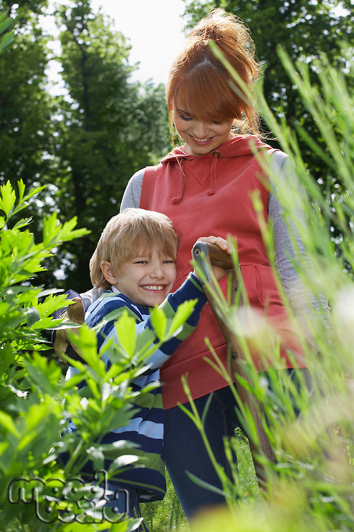 Mother embracing son (5-6) in garden