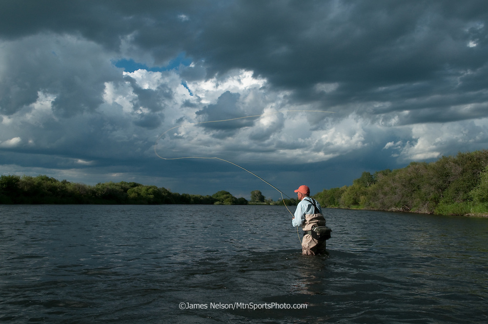 An angler casts a fly for trout on the lower Henry's Fork of the Snake River, Idaho.
