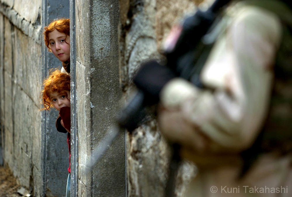 Girls watch the U.S soldiers patrolling the streets in Mosul in Feb 2005.