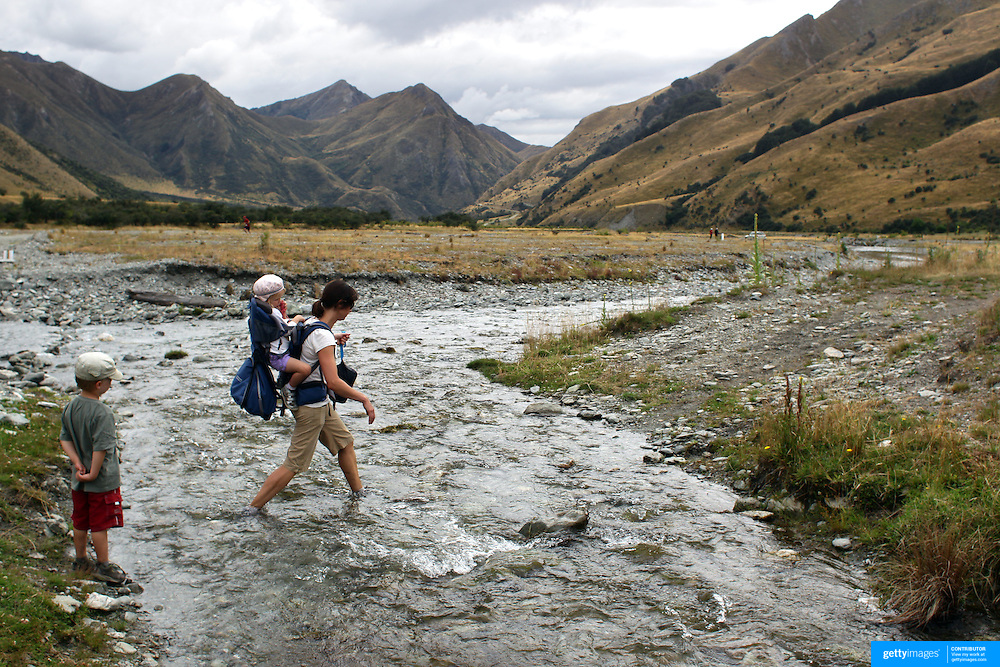 Runners Saskia Schenk, Alisa Schenk and Tom Schenk cross Moke Creek on the Ben Lomond High Country Station during the Pure South Shotover Moonlight Mountain Marathon and trail runs. Moke Lake, Queenstown, New Zealand. 4th February 2012. Photo Tim Clayton