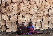 Masai children sit against the wall of their dry mud brick home June 18, 2003 in a village in Tanzania.
