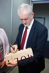 © Licensed to London News Pictures. 20/02/2016. Llandudno UK. Picture shows Labour leader Jeremy Corbyn signing a bottle of Champagne with the words Champagne Socialist after he delivered his keynote address at the Welsh Labour Party Conference 2016 in Llandudno, Wales. Photo credit: Andrew McCaren/LNP