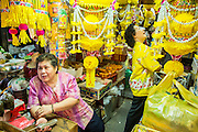 14 OCTOBER 2012 - BANGKOK, THAILAND:  A woman sells vegetarian festival supplies in Bangkok's Chinatown on the first day of the Vegetarian Festival.  The Vegetarian Festival is celebrated throughout Thailand. It is the Thai version of the The Nine Emperor Gods Festival, a nine-day Taoist celebration beginning on the eve of 9th lunar month of the Chinese calendar. During a period of nine days, those who are participating in the festival dress all in white and abstain from eating meat, poultry, seafood, and dairy products. Vendors and proprietors of restaurants indicate that vegetarian food is for sale at their establishments by putting a yellow flag out with Thai characters for meatless written on it in red.     PHOTO BY JACK KURTZ