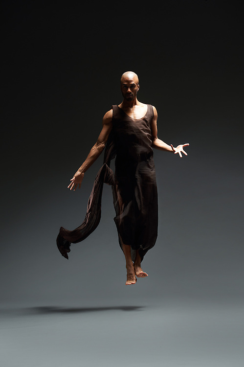 Contemporary male dancer, Anthony Savoy, in a brown dress by Epperson. Taken in the photo studio on a dark grey background. Photograph taken in New York City by photographer Rachel Neville.