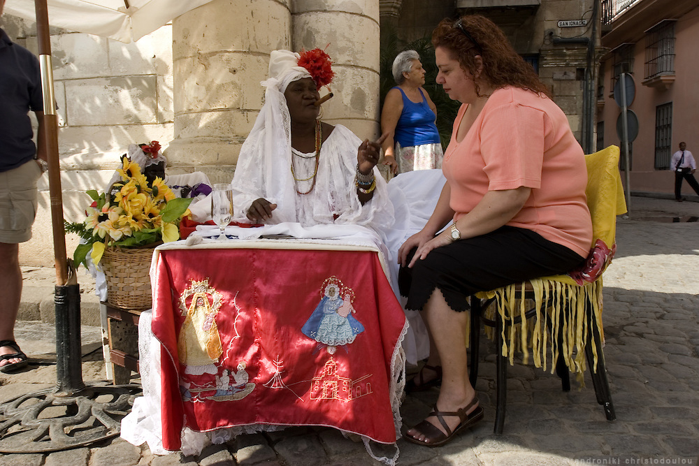 Fortune teller and priestess of Santeria religion, offering her services to a tourist in Plaza de Cathedral of Havana - CUBA