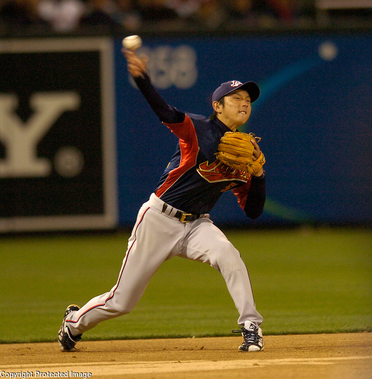 Team Japan's Munenori Kawasaki makes a play to first base in the 1st inning against Team Cuba in Final action of the World Baseball Classic at PETCO Park, San Diego, CA.