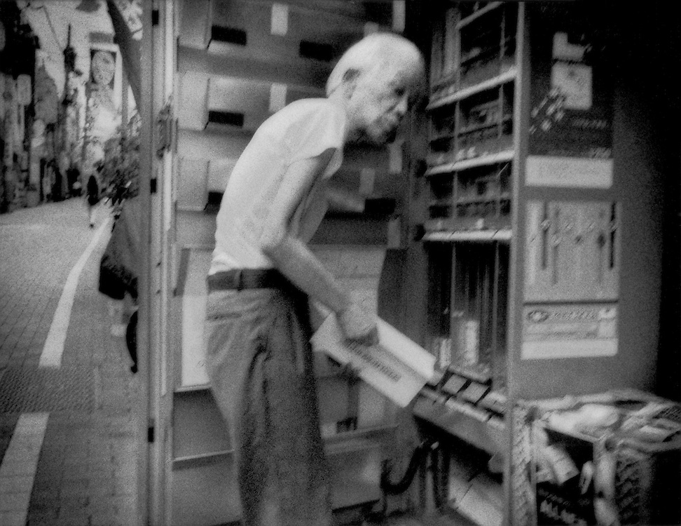 """Economic downturn leans hard on elderly / Elderly shopkeeper refills a cigarette vending machine in front of his family-run shoe store.   Hatagaya, Tokyo, Japan.  """"Ma & Pa"""" shops are in sharp decline which most effects the senior population for whom, since the end of the Second World War, the shops had provided their sole source of income.  The closure of a family shop can create a ruinous financial crisis for seniors.  These family shops, which used to be the mainstay for every community's shopping street or """"shotengai"""" are rapidly becoming """"shuttered streets"""" due to deregulation in the Japanese market followed by the biggest global economic crisis in a generation.  Such a crisis can drive seniors into de facto hiding."""