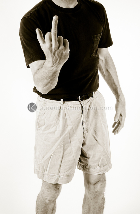 Front view of mature man making an obscene hand gesture, face is not visible.  Three quarter length studio shot against a light background. (releasecode: jk_mr1025) (Model Released)