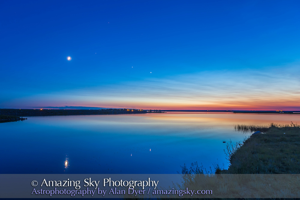 The evening planets of Venus (right) and Jupiter (left), to the right of the waxing crescent Moon on the evening of summer sosltice, June 21, 2015. The star Regulus is to the upper right of the Moon, between Jupiter and the Moon. The view is overlooking Crawling Lake in southern Alberta. This is an HDR stack of 5 exposures to retain detail in the bright twilight sky and the dark foreground.