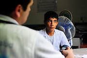 A teenage boy listens to a doctor from the 'Nefrolempa' health project, explain the results of his medical tests, as part of a series of medical investigations into the high incidence of chronic renal failure in the region.<br /> <br /> Community of Nueva Esperanza, Bajo Lempa, El Salvador. 2011<br /> The 'Nefrolempa' research project is a collaboration between the El Salvador Ministry of Health, the Nephrology Institute of Cuba's Ministry for Public Health and the United Bajo Lempa Committee Association. The aim of the project is to investigate the reasons for the high levels of Chronic Kidney Disease (CKD) suffered by the communities within the Bajo Lempa region. It is exploring whether the use of agrochemicals might be a factor in the prevalence of the disease.<br /> The 'Nefrolempa' research project is a collaboration between the El Salvador Ministry of Health, the Nephrology Institute of Cuba's Ministry for Public Health and the United Bajo Lempa Committee Association. The aim of the project is to investigate the reasons for the high levels of Chronic Kidney Disease (CKD) suffered by the communities within the Bajo Lempa region. It is exploring whether the use of agrochemicals might be a factor in the prevalence of the disease.
