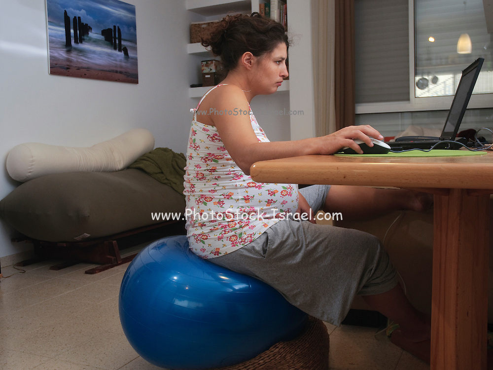 Pregnant woman in her 30s sits on a physiotherapy ball works from home on her laptop computer - Model release available