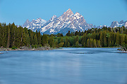 The Grand Teton rises above the Snake River before sunrise in Grand Teton National Park, Jackson Hole, Wyoming
