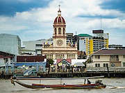 18 SEPTEMBER 2016 - BANGKOK, THAILAND:  A long tail boat, taking tourists down the Chao Phraya River, goes past Santa Cruz Church. Santa Cruz Church was establised in 1769 to serve Portuguese soldiers in the employ of King Taksin, who reestablished the Siamese (Thai) empire after the Burmese sacked the ancient Siamese capital of Ayutthaya. The church was one of the first Catholic churches in Bangkok and is one of the most historic Catholic churches in Thailand. The first sanctuary was a simple wood and thatch structure and burned down in the 1800s. The church is in its third sanctuary and was designed in a Renaissance / Neo-Classical style. It was consecrated in September, 1916. The church, located on the Chao Phraya River, serves as a landmark for central Bangkok.      PHOTO BY JACK KURTZ