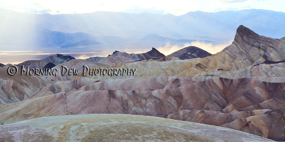 Heavy winds kick up a dust storm in the valley beyond the badlands at Zabriskie Point. Death Valley National Park, CA