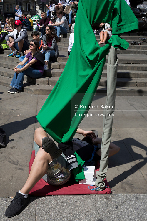 A street busker sleeps beneath his costume in Piccadilly Circus, on 9th May 2018, in London, England.