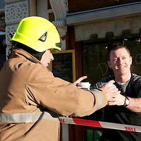 Freezing Perthshire....07.12.10  <br /> As temperatures plummeted overnight to minus 18, Tayside Fire & Rescue were inundated with 999 calls regarding dangerous ice hanging from buildings...Pictured Gary Blease whose shop was affected by ice handing over coffee to Firefighter Kevin McKay.<br /> Picture by Graeme Hart.<br /> Copyright Perthshire Picture Agency<br /> Tel: 01738 623350  Mobile: 07990 594431