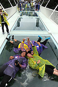 ZHANGJIAJIE, CHINA - JUNE 25:<br /> <br /> Visitors lie on glass-bottomed bridge for a selfie during the safety test at Zhangjiajie Grand Canyon on June 25, 2016 in Zhangjiajie, Hunan Province of China. World\'s tallest and longest glass-bottomed bridge has been completed and took a global broadcast through television and internet medias to show its safety. More than thirty citizens and visitors thumped the bridge with hammer in the test event. <br /> ©Exclusivepix Media