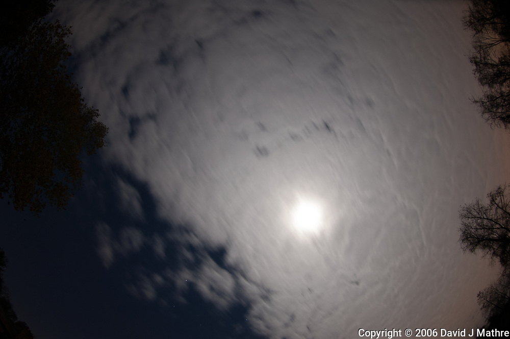 Moon behind a cloud layer blocking the night sky. Image taken with a Nikon D2xs camera and 10.5 mm f/2.8 fisheye lens (ISO 100, 10.5 mm, f/2.8, 15 sec).