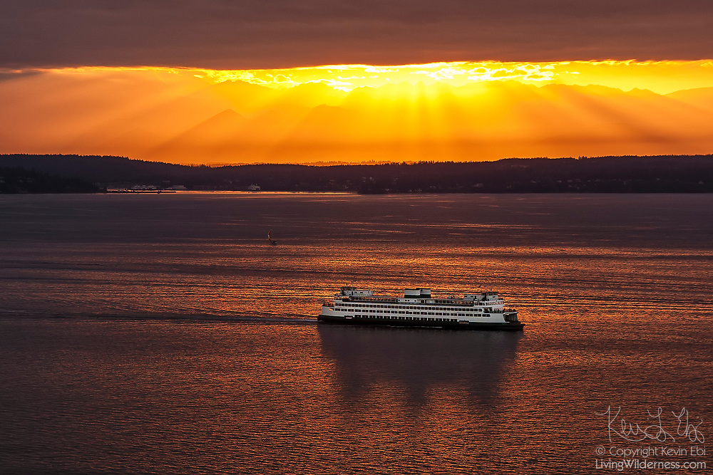 As the sun nearly breaks through the clouds just before sunset, dramatic beams, called crepuscular rays, form over a ferry crossing Puget Sound.