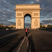 The Arc de triomphe in Paris during the golden hour.