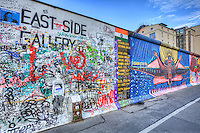 "The East Side Gallery is an international memorial for freedom. It is a 1.3 km long section of the Berlin Wall located near the centre of Berlin on Mühlenstraße in Friedrichshain-Kreuzberg. The actual border at this point was the river Spree. The gallery is located on the so-called ""hinterland mauer"", which closed the border to East Berlin and it consists of 105 paintings by artists from all over the world, painted in 1990 on the east side of the Berlin Wall."
