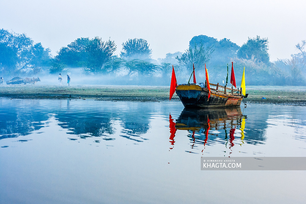 A boat parked on the bank of Yamuna river with people on the side having an early morning conversation Mathura is a sacred town situated on the banks of Yahuman river in Uttar Pradesh, northern India. The birthplace of the deity Lord Krishna. It is a pilgrimage site for Hindus.