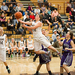 McKenzie Johnston (32) leaps past the Butte High defense for a basket during 3rd quarter action at Capital High School.