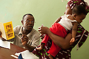 Volunteer Komba D. Musa speaks to a mother and her child at the Kono government hospital in Koidu, Sierra Leone on Wednesday March 17, 2010..