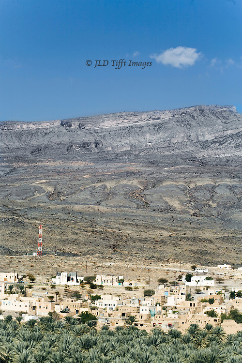 Landscape of Oman, with grove of palm trees, mud brick and plaster dwellings in a village, red and white tower carrying high tension wires, backed by bare mountain slopes.