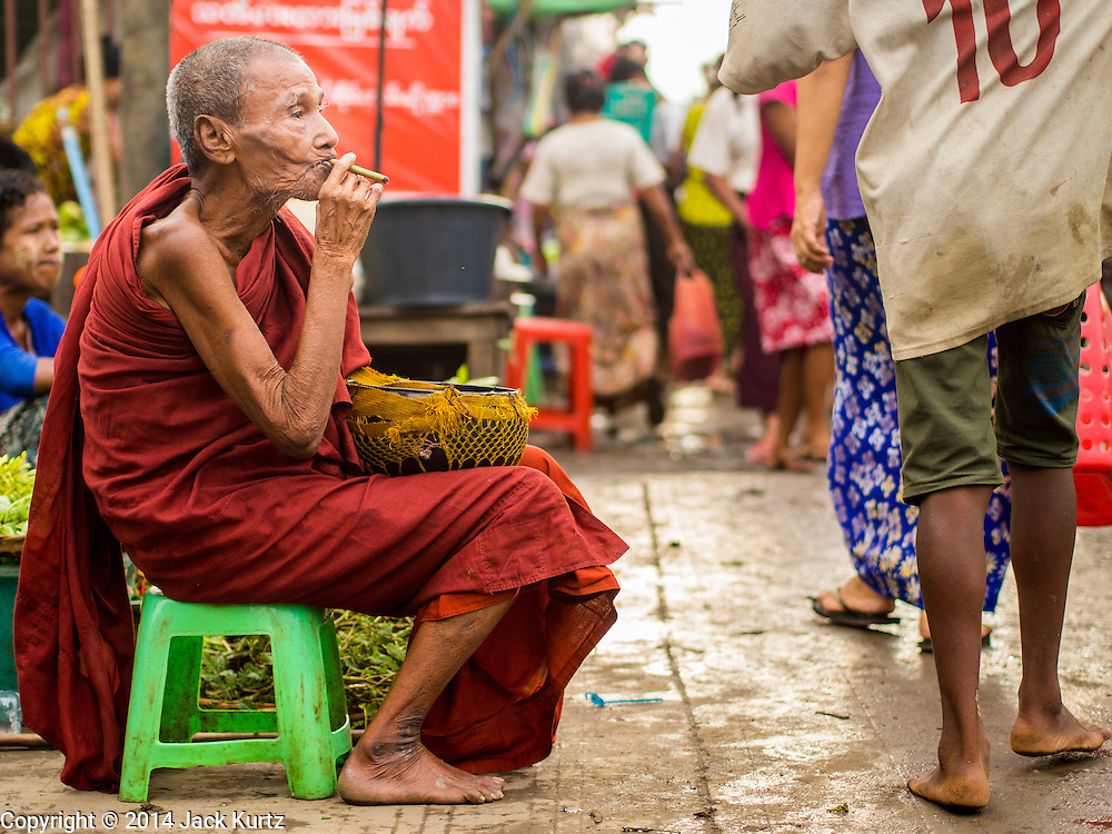 08 NOVEMBER 2014 - SITTWE, RAKHINE, MYANMAR:  A Buddhist monk with a Burmese cheroot solicits alms at the entrance to the market in Sittwe. Sittwe is a small town in the Myanmar state of Rakhine, on the Bay of Bengal.  PHOTO BY JACK KURTZ