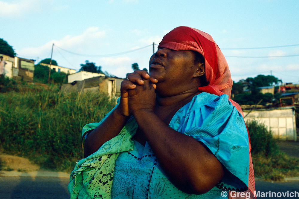 KwaMashu township, KwaZulu Natal, Durban, South Africa. Woman prays and mourns after deaths in Lindelani informal settlement in KwaMashu aftern clashes between African National Congress and Inkatha Freedom Party supporters, 1994.