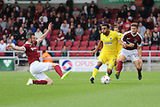 Northampton Town defender Zander Diamond (5) slides to stop AFC Wimbledon striker Andy Barcham (17) and Northampton Town defender Aaron Phillips (18) during the EFL Sky Bet League 1 match between Northampton Town and AFC Wimbledon at Sixfields Stadium, Northampton, England on 20 August 2016. Photo by Stuart Butcher.